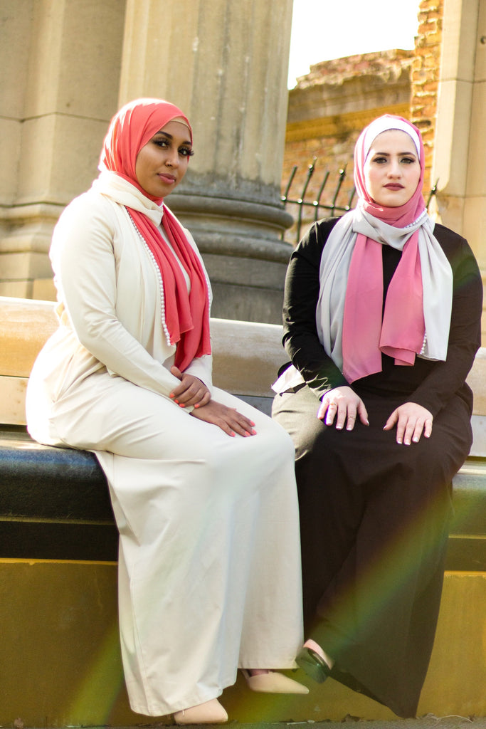two muslim friends wearing long sleeved maxi dresses and a hijab in pink and silver decorated with pearls