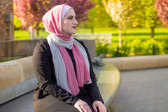 muslim woman on a park bench wearing a black dress and a hijab in pink and silver decorated with pearls