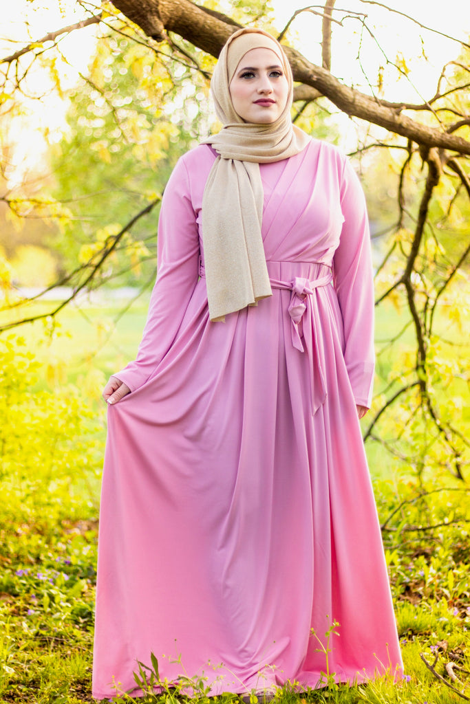 muslim woman wearing a gold shimmer jersey hijab and pink criss cross maxi long sleeve dress with pockets and a waist tie
