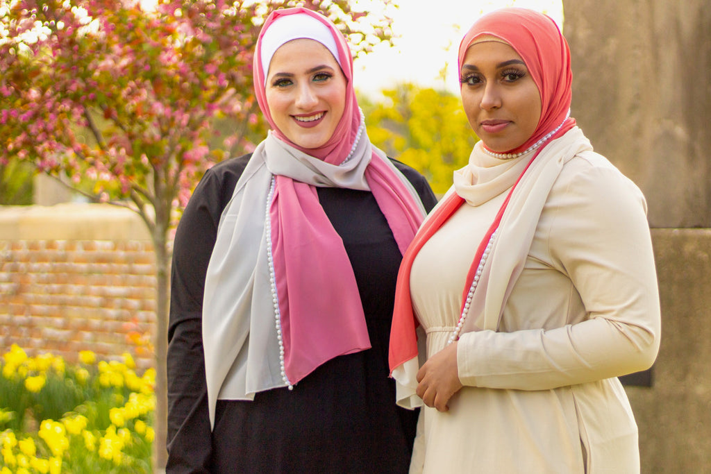 two muslim women wearing long sleeved maxi dresses and pearl hijabs