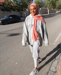 muslim woman walking down the street wearing all gray and a mauve bamboo hijab