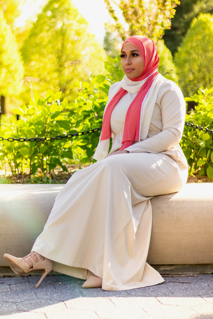 black muslim woman in a creme long sleeve maxi dress and pearl hijab