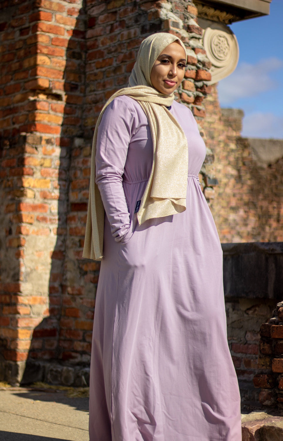 muslim woman wearing a lavender long sleeve maxi dress and a sparkly gold jersey hijab