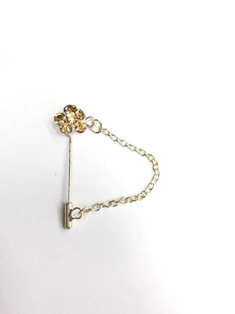 silver clasp pin with gold floral jewel and a chain