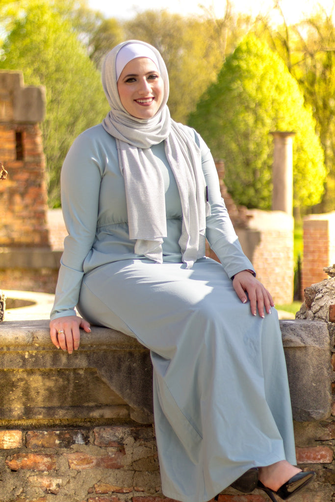 muslim woman in a sparkly silver jersey hijab and a light blue long sleeved maxi dress