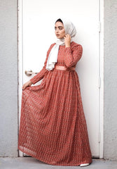 muslim woman wearing a long sleeve maxi dress in burnt orange lace with a satin waist tie and satin gray hijab