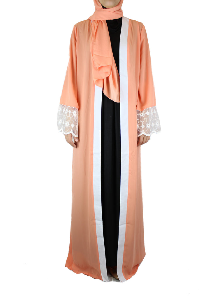 woman wearing an abaya in salmon embellished with lace sleeves and a matching hijab