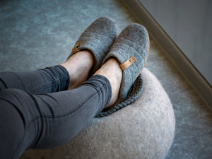 A woman wearing Cocoon felted wool slippers with collapsible backs, with her legs on a felted wool ball.