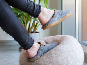 A woman wearing easy to slip on  COCOON slippers, stepping on a felted wool ball