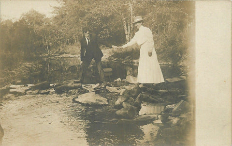 RPPC Gentleman Takes Hand to Help Victorian Lady Across River on Rocks~c1918 pc