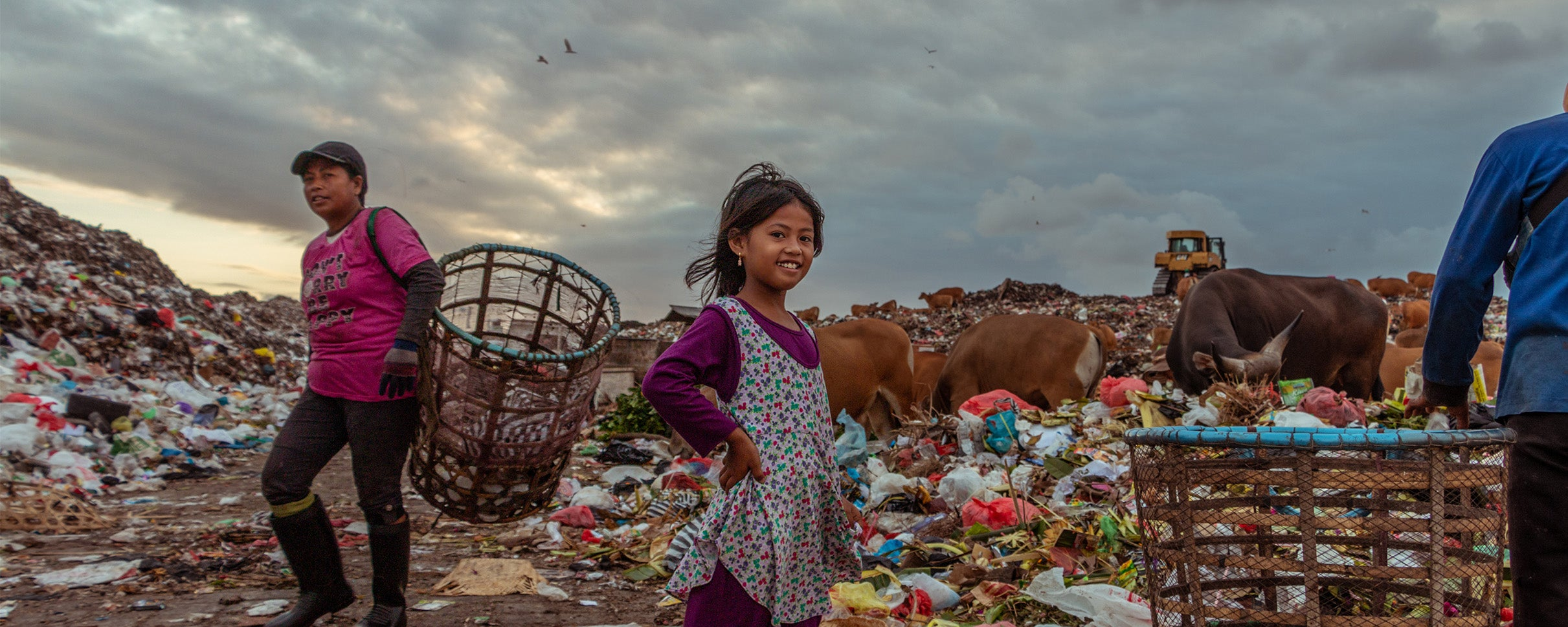 A young girl smiles for the camera despite growing up on a landfill.