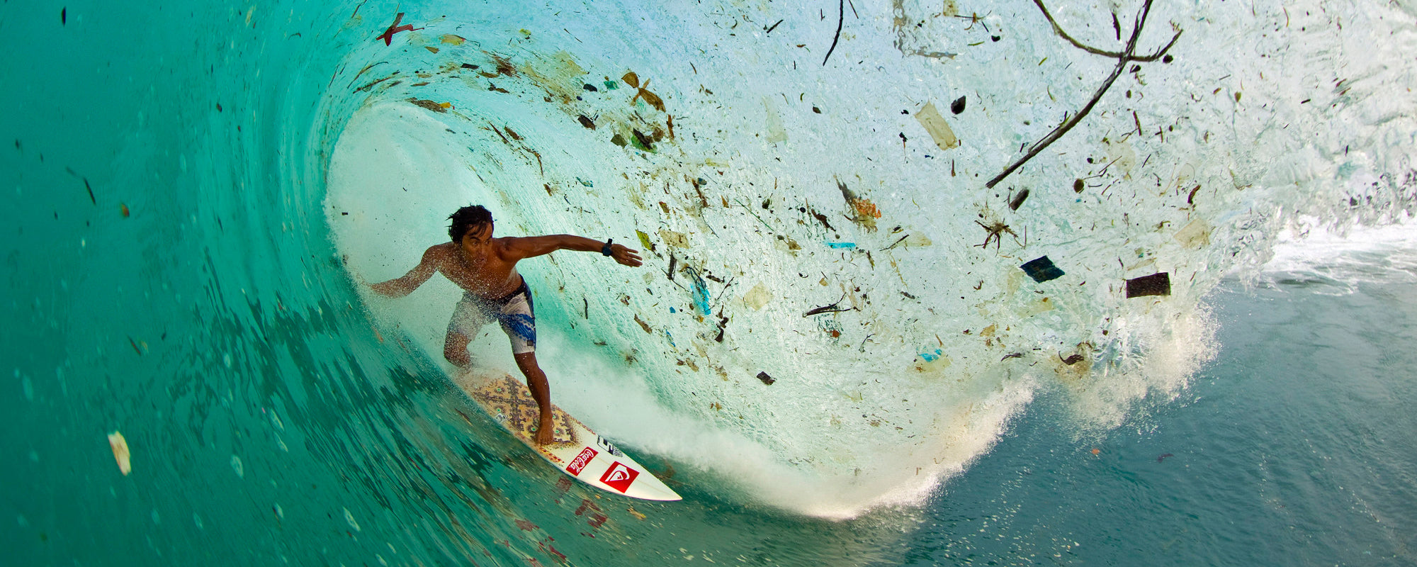 Surfer surrounded by plastic in Bali - Zak Noyle