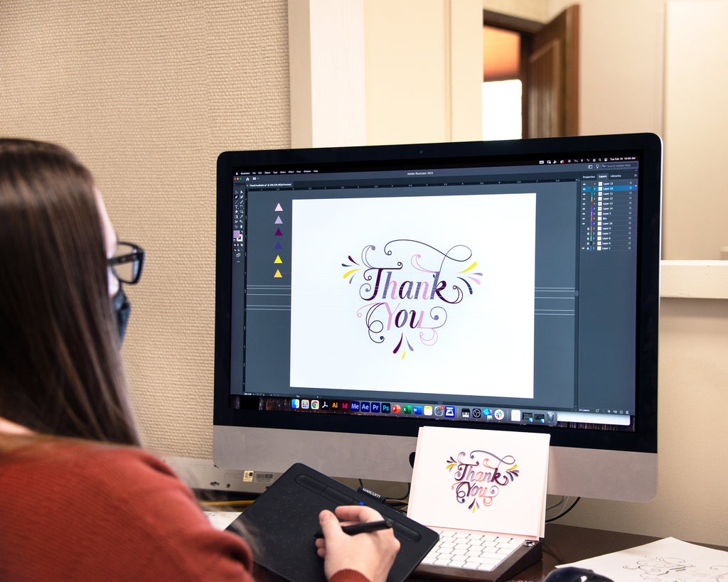 Graphic designer editing an image on a computer screen.