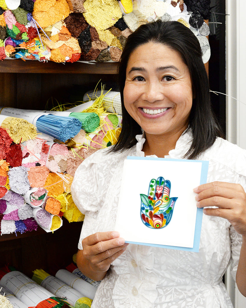Huong holding a quilled card.