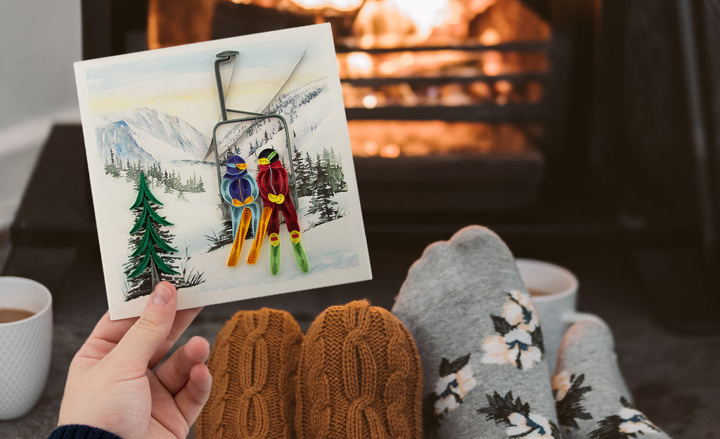 A hand holding the Quilled Ski Lift Greeting Card while sitting in front of an open fire.