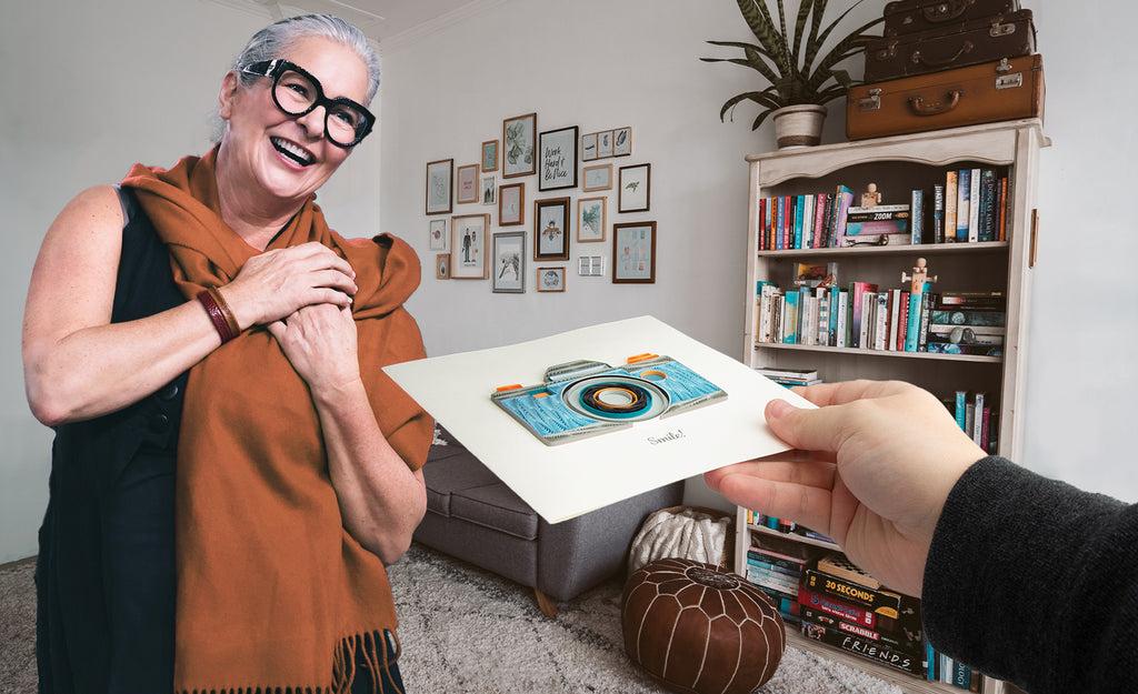 A hand offering the  Quilled Camera Greeting Card to a smiling woman.