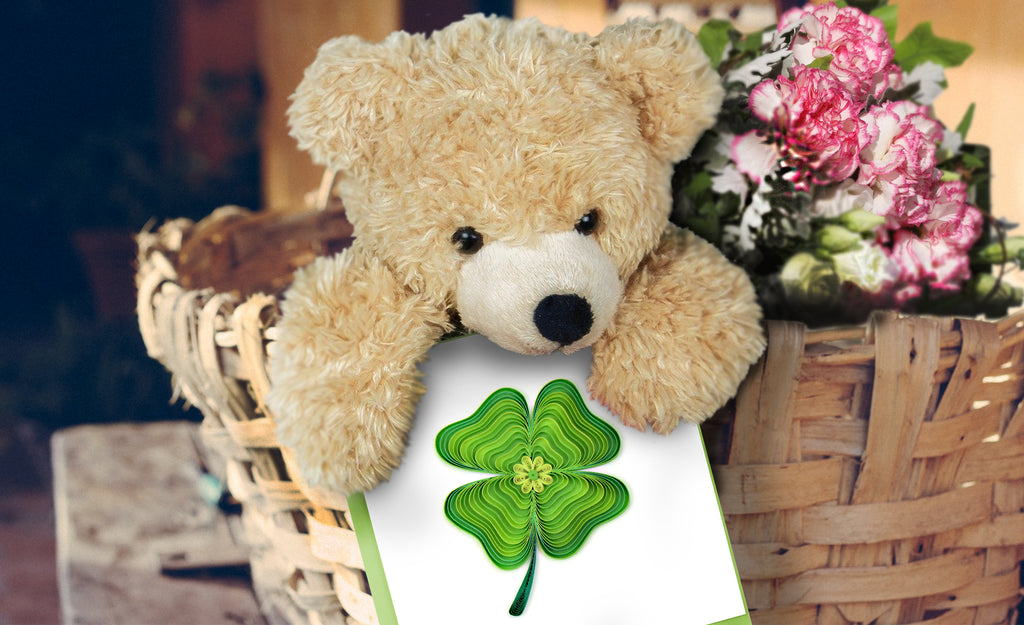 A teddy bear holding the Quilled Four Leaf Clover Card.