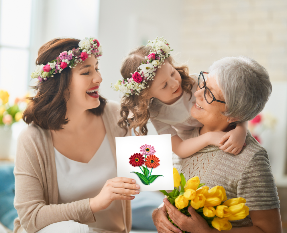 Mother and daughter giving grandmother a card