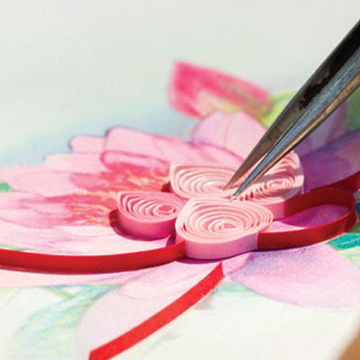 Artisan gluing papers onto card.