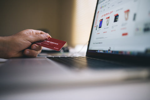 A laptop computer with a hand holding a credit card ready to make a purchase.