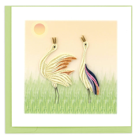 Two white cranes standing in a green field in front of an orange sky.