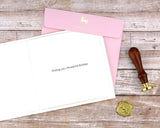 Pink envelope, insert with printed sentiment, and wax seal that accompany the greeting card