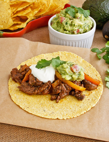 Skillet Beef Fajitas with sour cream and guacamole.
