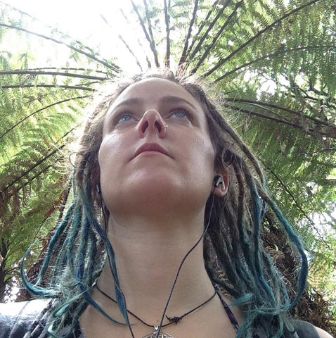 close up of girls face from below looking up as she walks through trees with dreadlocks