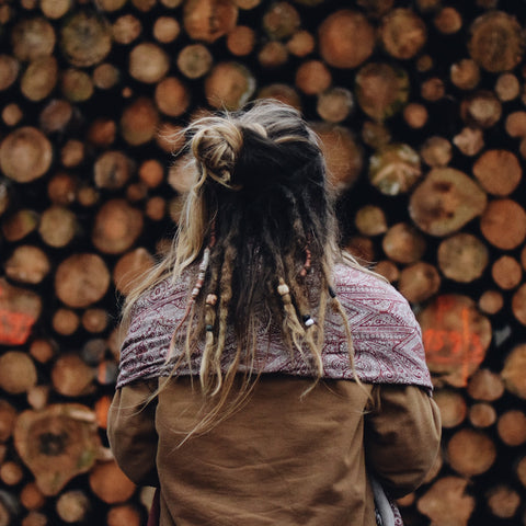 Woman with dreadlocks facing away and sitting infront of wood piles