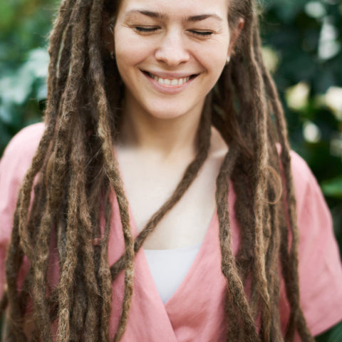 Woman with dreadlocks looking down and smiling