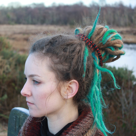 Girl with dreadlocks looking to the left with spiral hair tie in hair