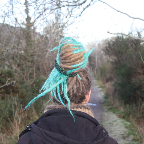 girl with dreadlocks walking away down a path with her hair tied up with a spiral hair tie