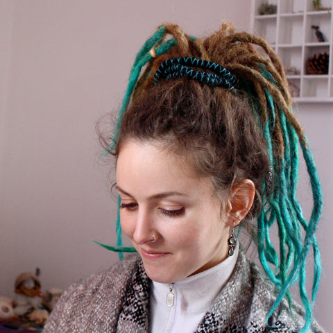 girl with dreadlocks looking down with her hair tied up with a bendable spiral hair tie