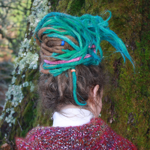 girl with dreadlocks looking away with a hair tie in her hair