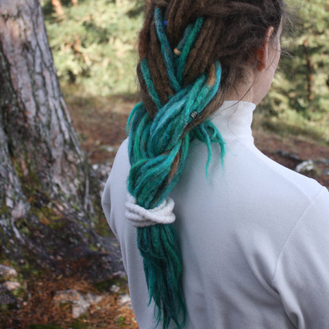 girl looking away with dreadlocks with her hair braided and tied together with a spiral hair tie