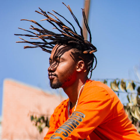 Man with dreadlocks flicking hair into the air