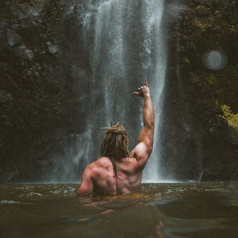 Man in water with dreadlocks holding up right hand with fist into the direction of a waterwall