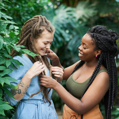 two girls with dreadlocks facing eachother and playing with left hand side girls hair