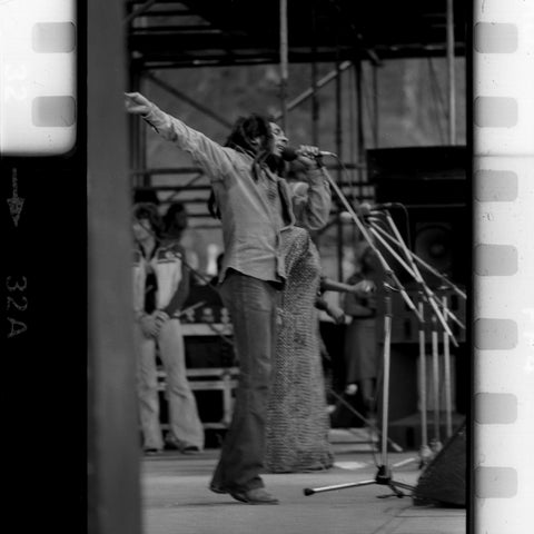 bob marley singing on stage with arms in air