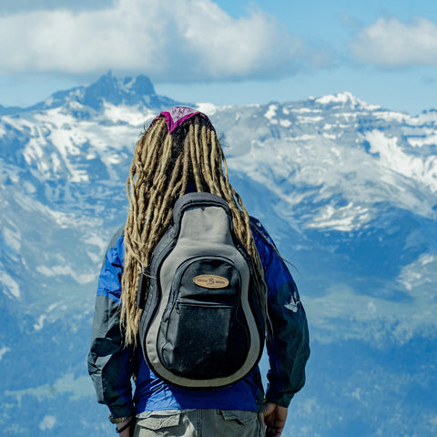 Man with dreadlocks looking out to mountains in the distance