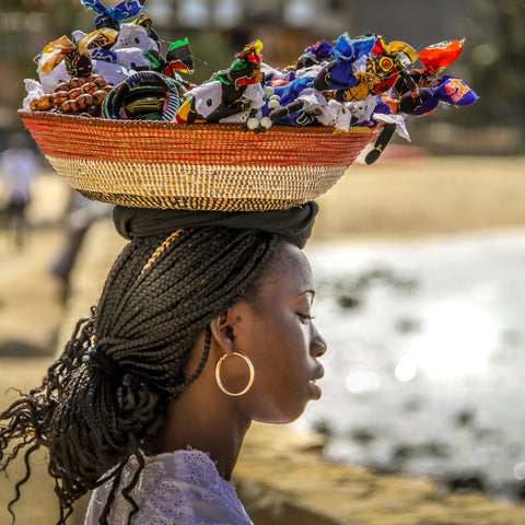 A beautiful Cape Verdian woman, carrying a basket of trinkets on her head, to sell to the tourist