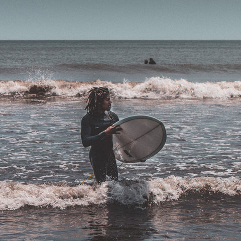 Man with dreadlocks wearing wet suit holding surfboard walking out of the sea