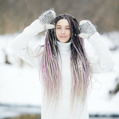 Woman in snow holding up hands with dreadlocks