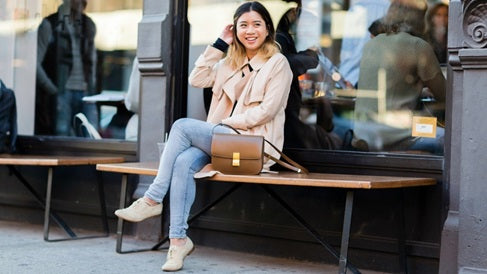 woman sitting on a bench wearing a beige jacket, denim pants and beige shoes