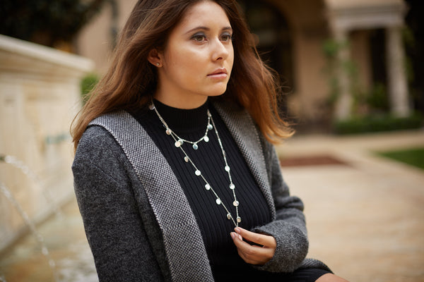 woman with silver necklace, model posing, photoshoot model, woman wearing a nice sweater, sweater model based in los angeles california, model sitting for a photo shoot, fashion sweater styling, model based in los angeles for a photo shoot