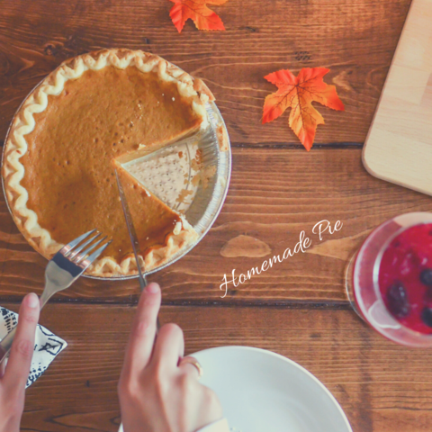 person slicing a piece of pumpkin pie on a wooden table