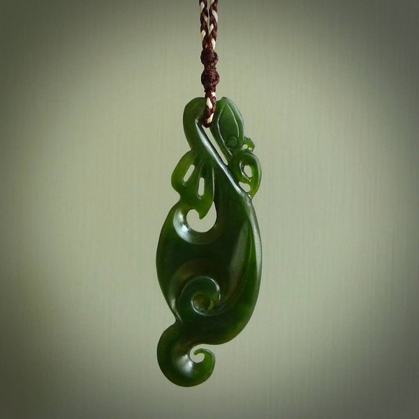 This picture shows a matte manaia pendant carved for us by Ross Crump. It is a dark matte green colour in  traditional manaia design. Ross has added a koru on the bottom which elongates the carving and gives it some decorative flair. We have plaited a cord in dark brown and white and made it length adjustable. This is a very beautiful piece of art to wear.