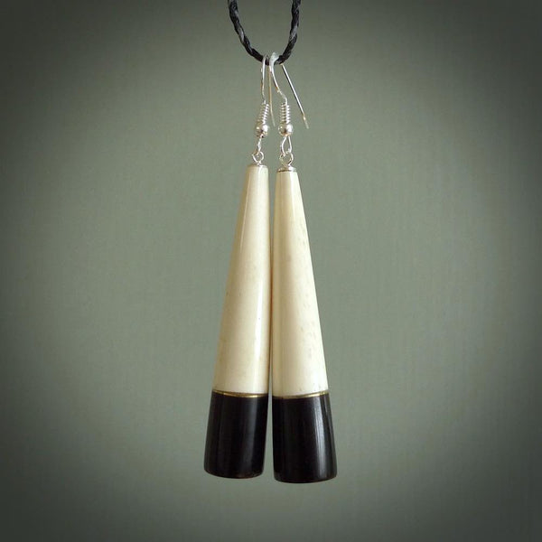 Hand carved earrings made from bone and buffalo horn. They are an elongated drop shape with a flat bottom. The bone is a nice creamy white and incorporates the top three quarters, and the bottom quarter is a beautiful black buffalo horn. These are wonderful handcrafted earrings.