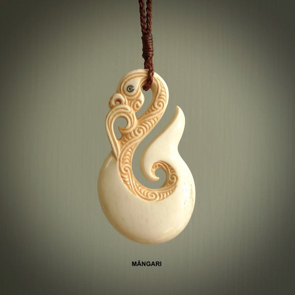 This picture shows a carved manaia in bone. It is a hook shaped pendant pendant that culminates in a fish tail. The artist has carved traditional decorative Koru designs into the side of the body and these run up the sides of the manaia head. These have specific meanings. It is provided with a hand-plaited brown cord that is length adjustable.