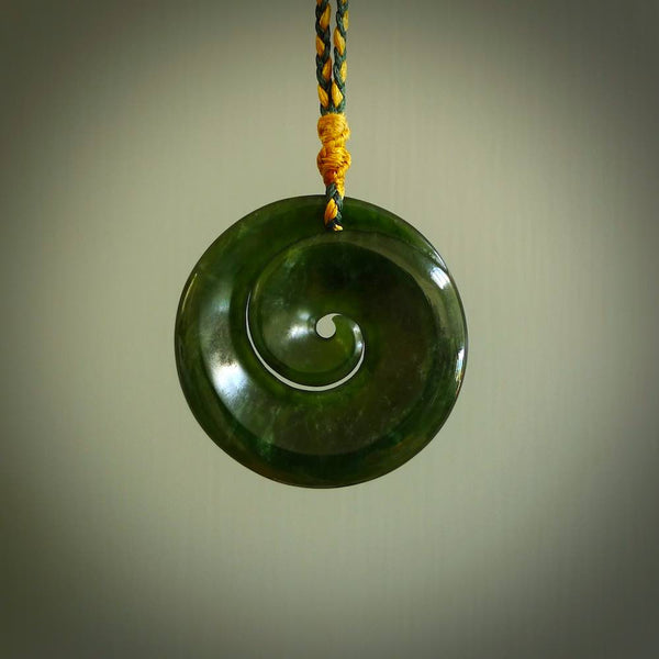 This picture shows a large dark green jade koru pendant. This is handcarved in New Zealand and is suspended on an adjustable Gold and Manuka Green coloured cord. These are shipped worldwide with no additional charge for postage.